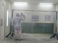 man-wearing-protective-suit-doing-powder-coating