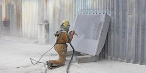 man-wearing-protection-suit-doing-sandblasting